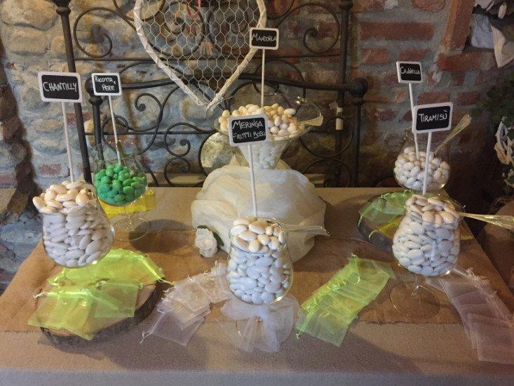 un tavolo con dei barattoli di confetti di diversi gusti e dei veli colorati