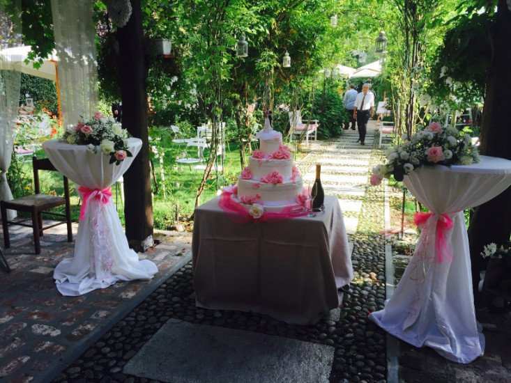 un tavolo con sopra una torta a 3 piani con delle rose fucsia e ai lati dei vasi con delle composizioni floreali in un giardino