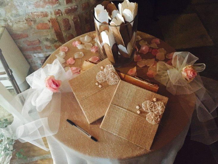 un tavolo con un barattolo con dentro delle piume,  dei veli con delle rose colorate e due libri ricoperti in iuta con dei fiori bianchi