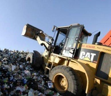 una scavatrice su dei rifiuti