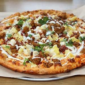 Pizza di pollo e ananassi con mozzarella fresca e un tocco di rucola