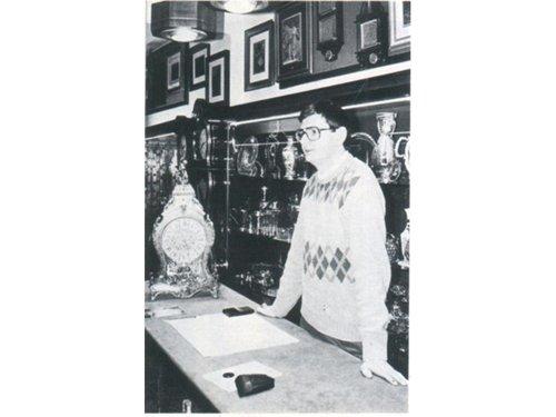 foto in bianco e nero di un orefice dietro al bancone di una gioielleria