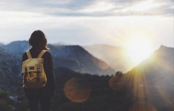 una ragazza con uno zaino che guarda le montagne