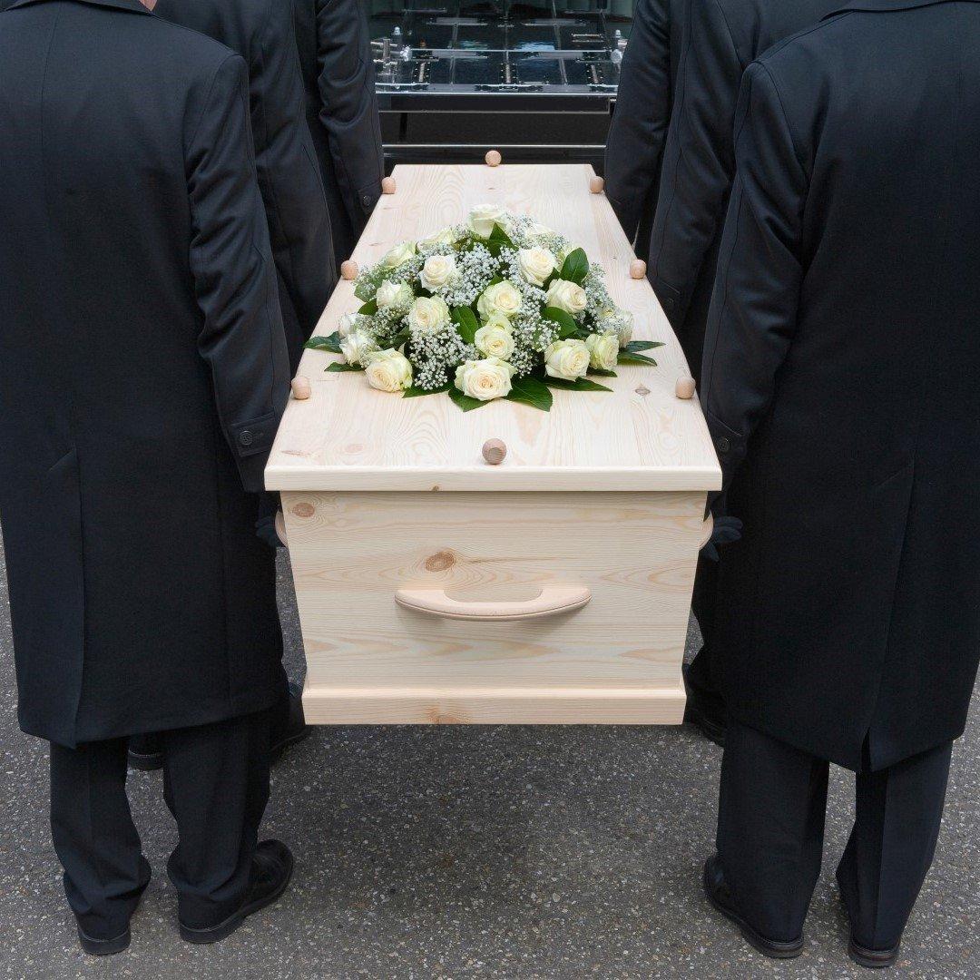 Una bara in legno con una composizione floreale trasportata a mano da sei uomini vestiti in nero