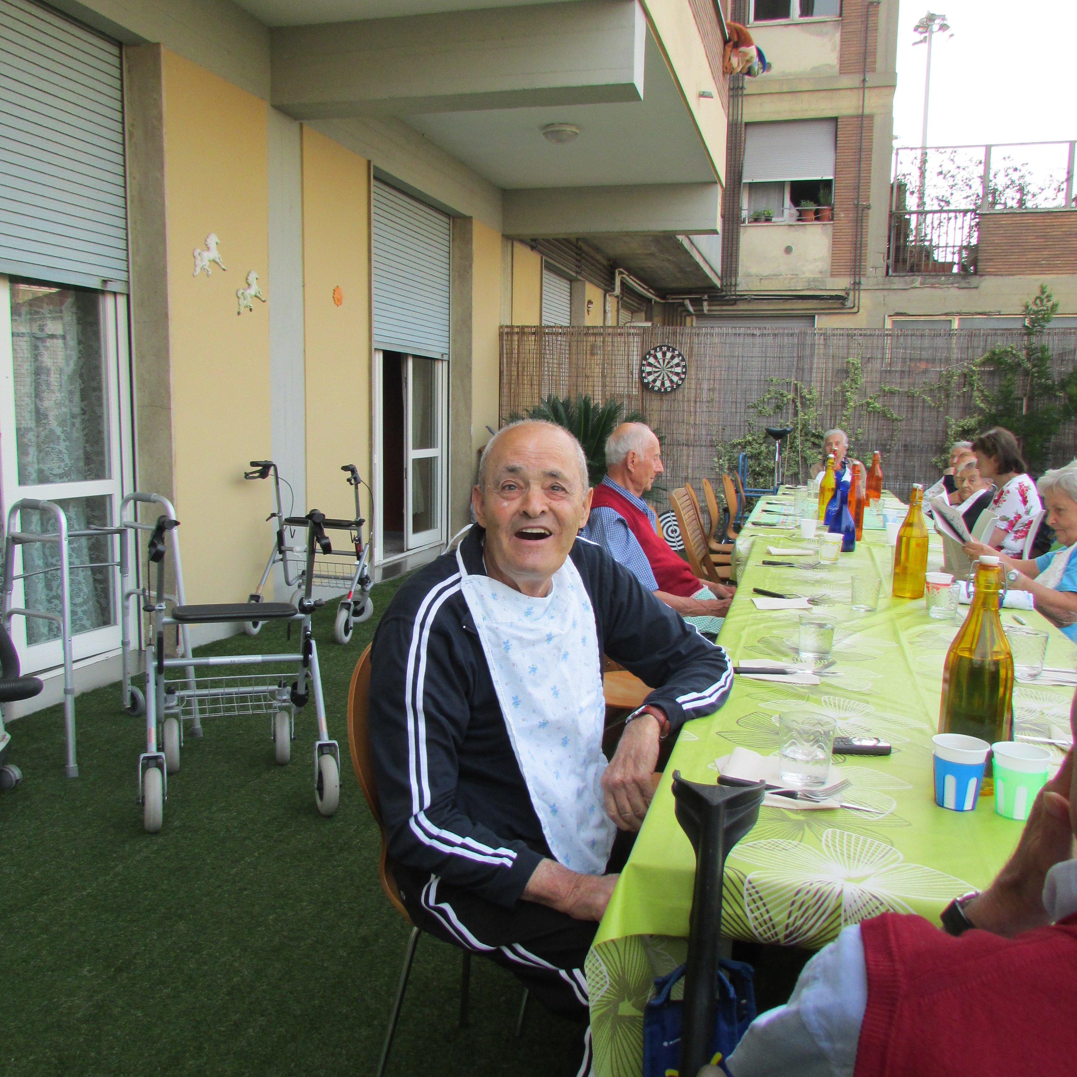 tavolata per pranzo all'aperto con primo piano persona anziana sorridsente