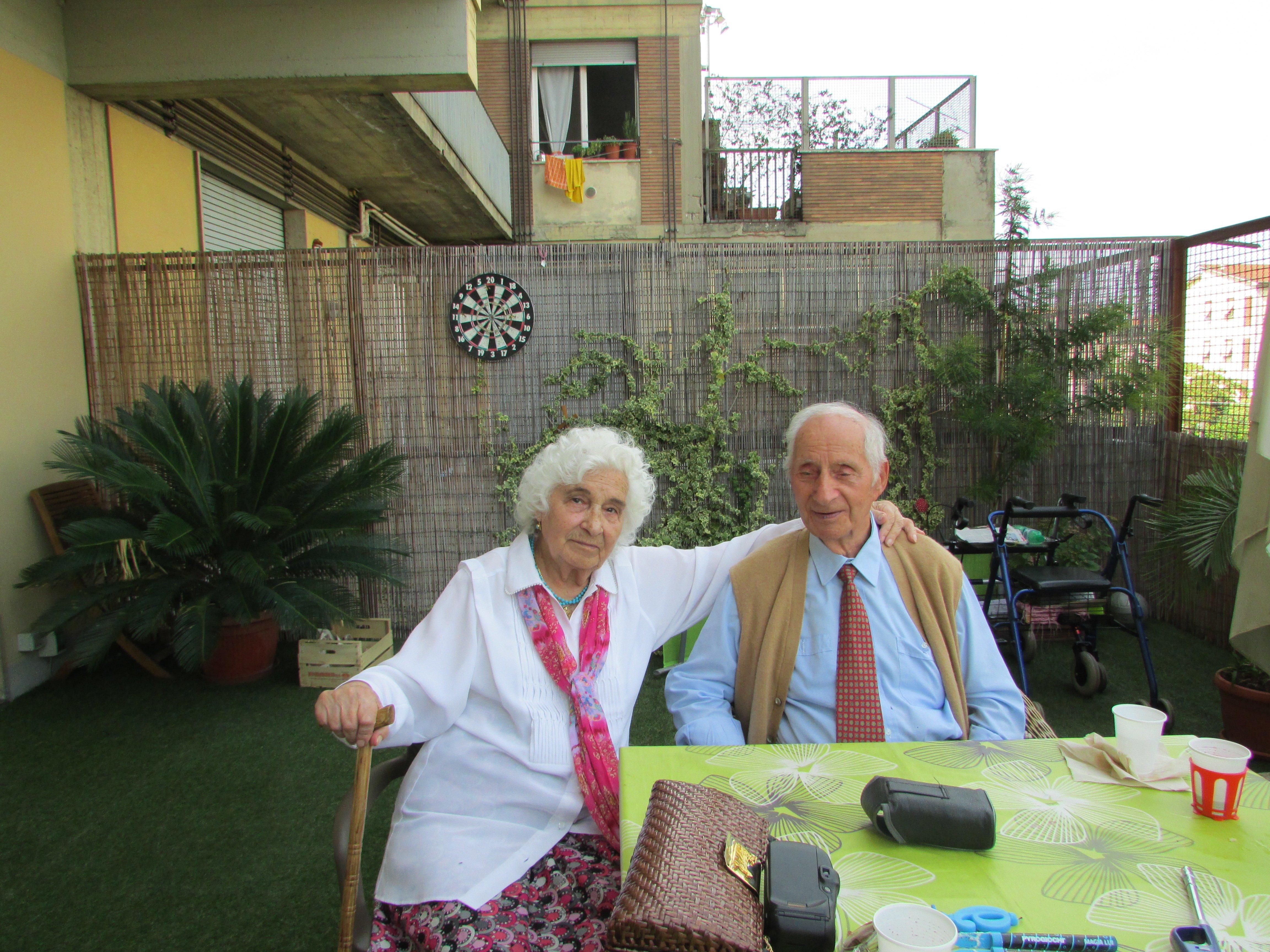 coppia di anziani seduti ad un tavolo all'aperto
