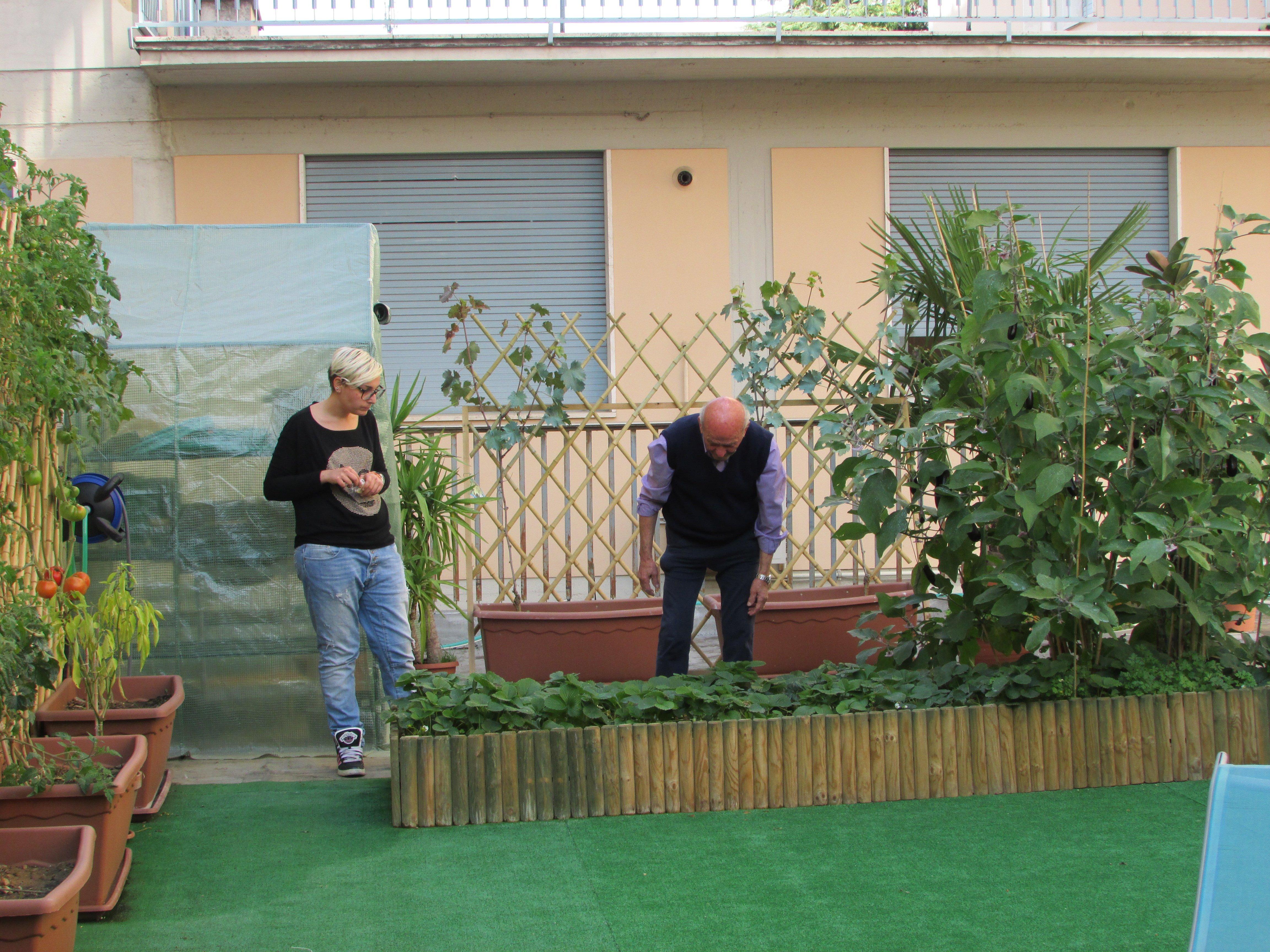 due persone che curano l'orto sul terrazzo