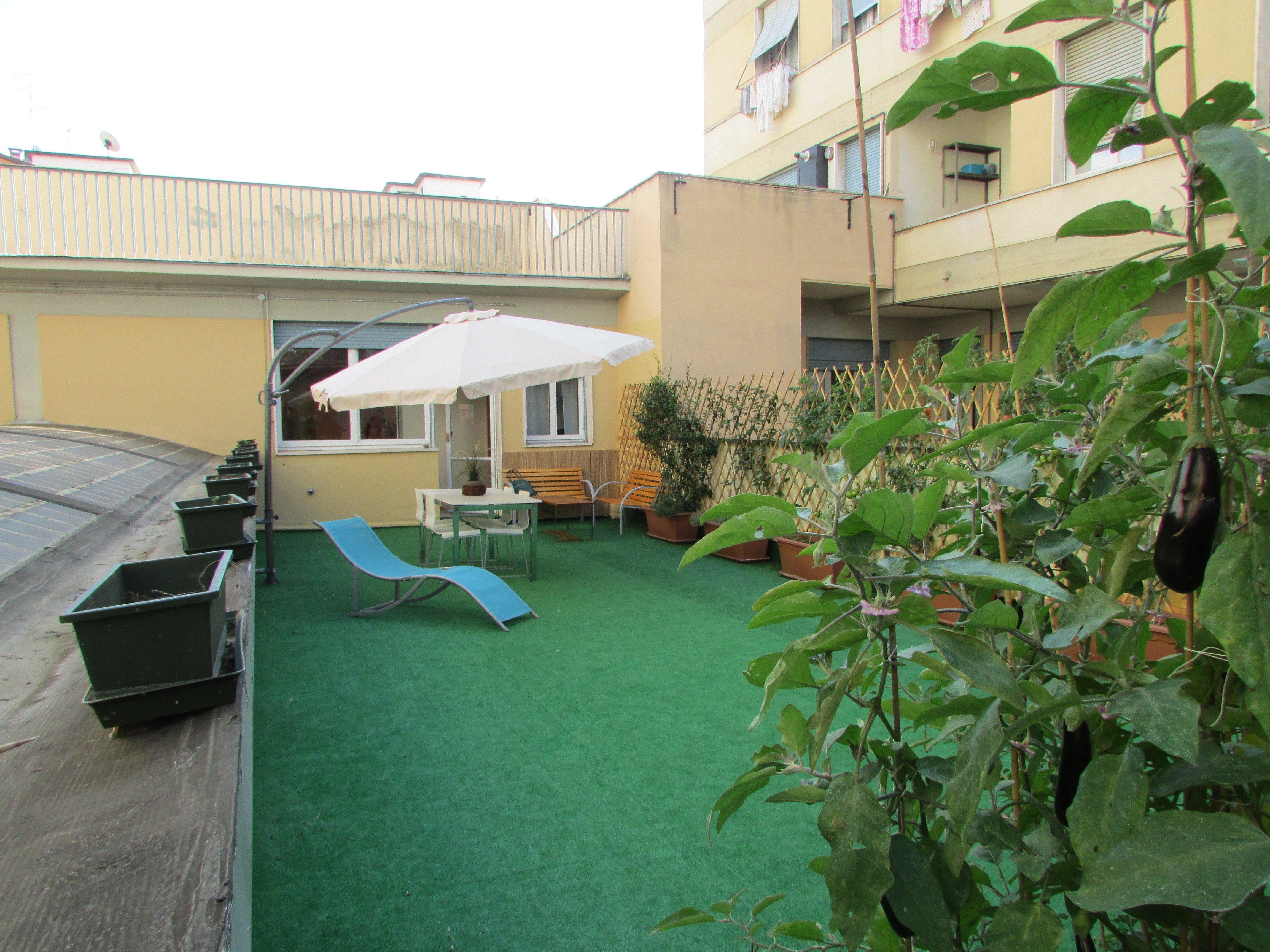 terrazzo con ombrellone e sdraio