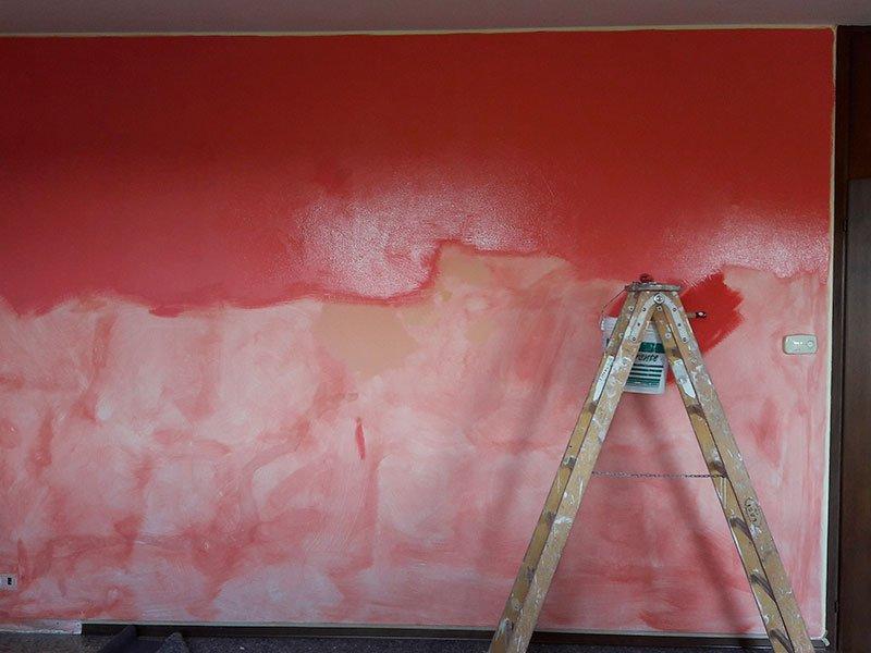 Un muro verniciato di rosso con  sfumature bianche e una scala in ferro