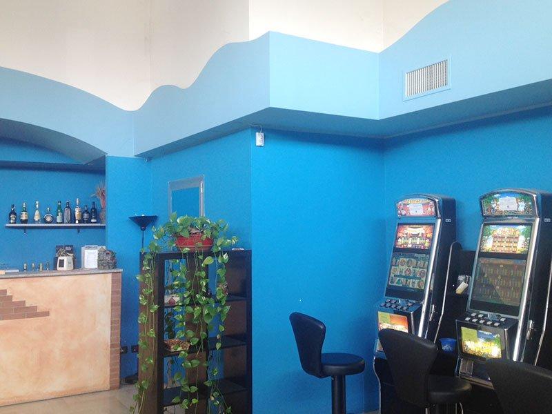 delle pareti blu e sulla destra delle slot machine