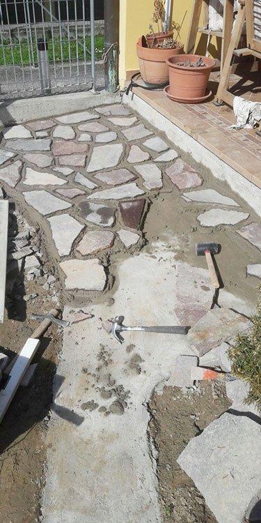 una pavimentazione in roccia in un giardino e due martelli
