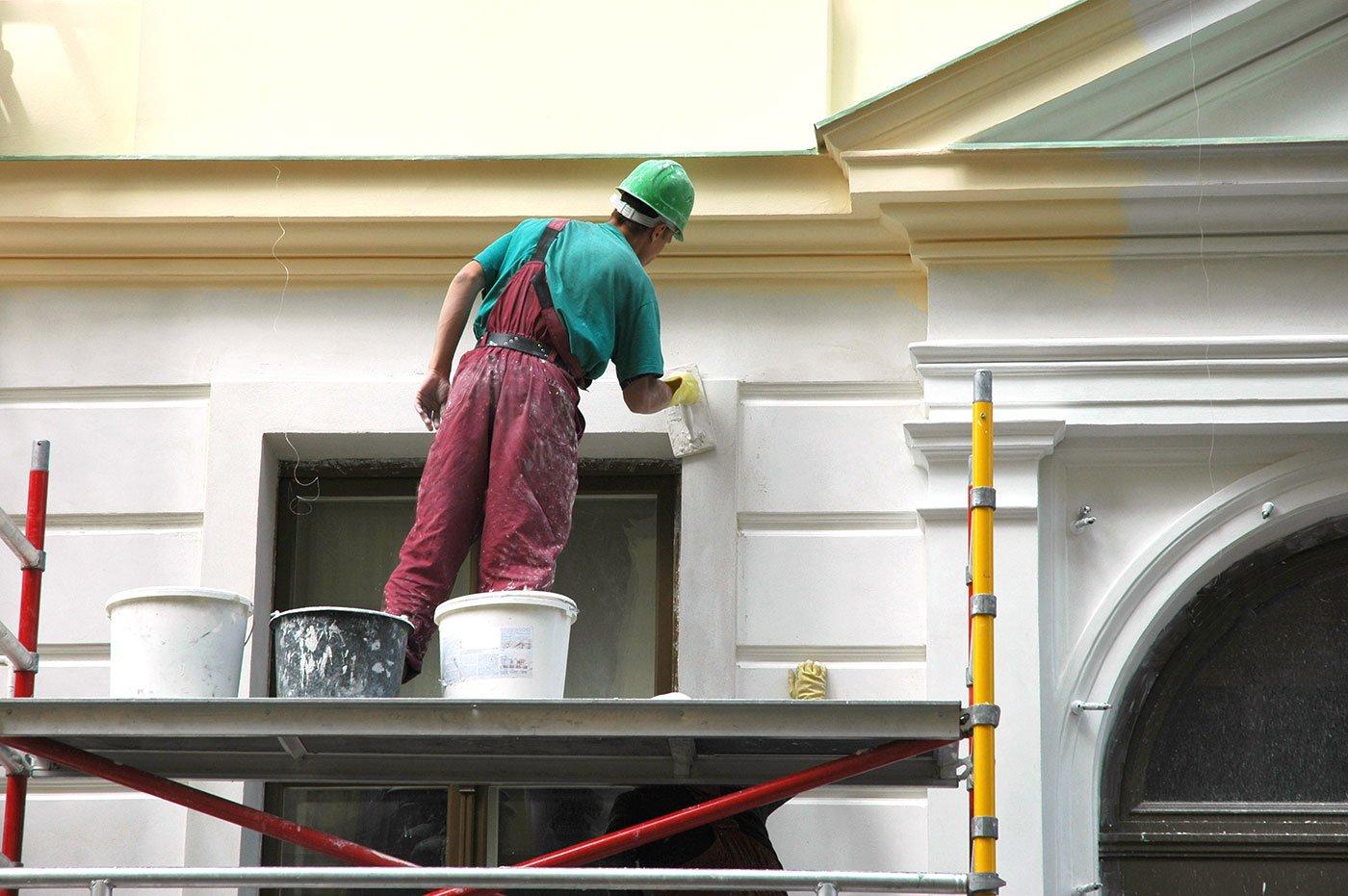 un imbianchino con un elmetto verde che imbianca una facciata di una casa