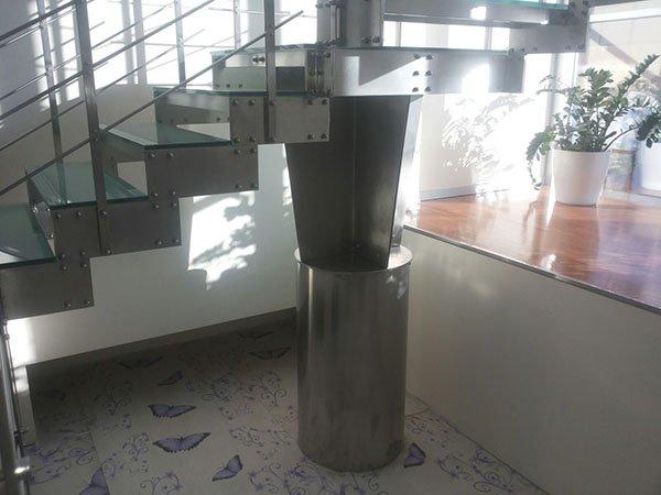 scale interne in acciaio e vetro sorrette da un pilone in ferro