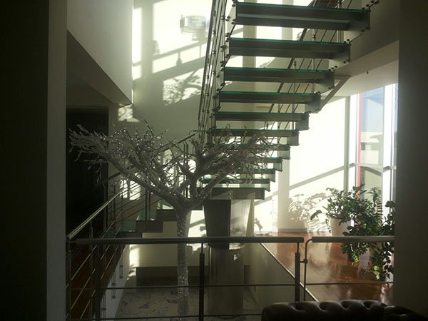 scala interna con pioli in vetro e un giardinetto sotto