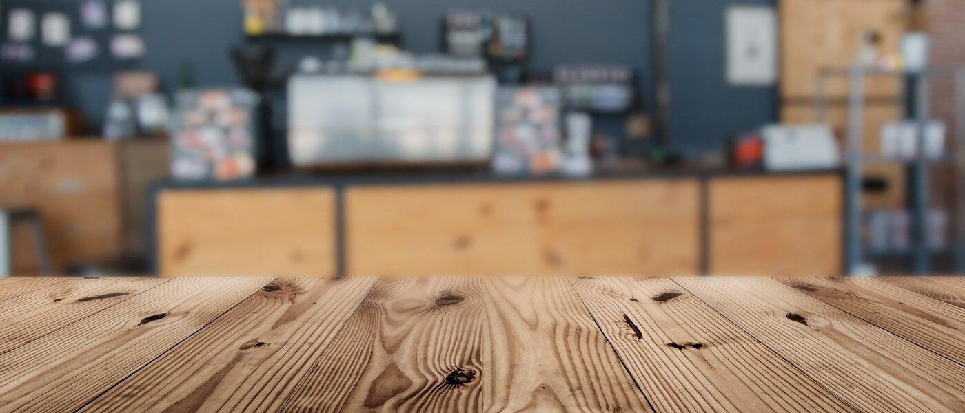 Superficie di un tavolo in legno con sfondo sfuocato degli interni di un negozio a Palermo