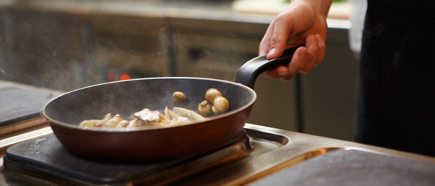 Chef cucina funghi in padella
