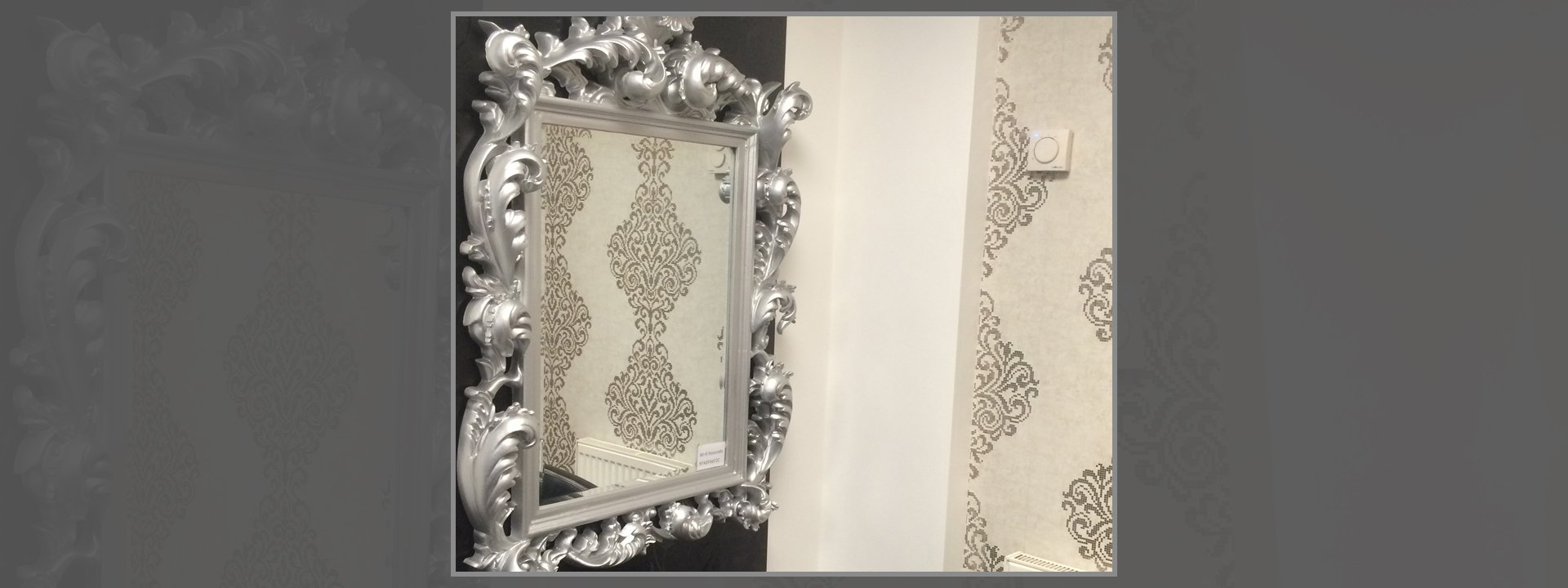 Cream patterned wall reflected in a mirror with ornate silver frame