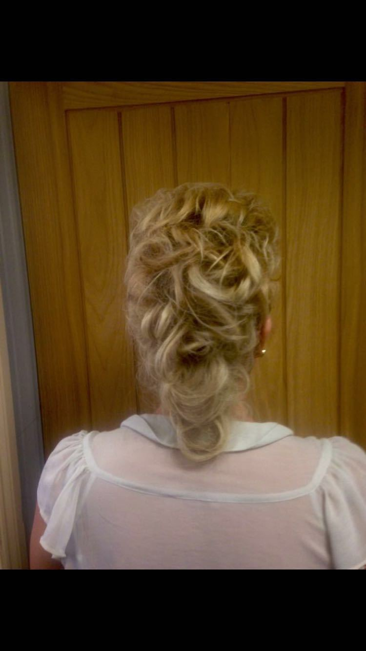 Blonde hair taken back in a curly pony tail