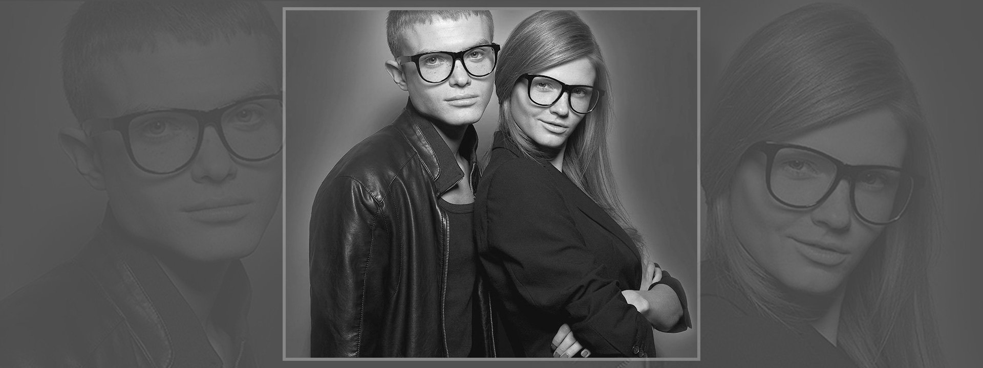 A young man with cropped hair, and young lady with long hair, both wearing large framed horn rimmed glasses