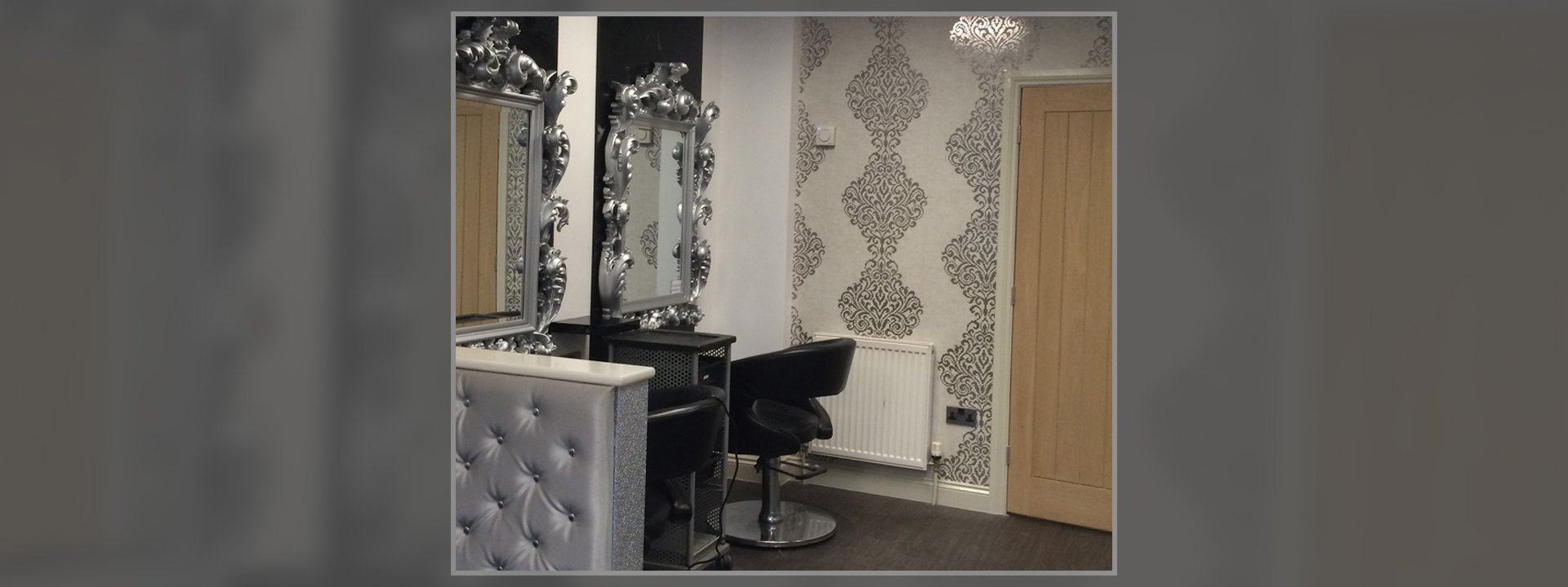 Black leather chairs in front of mirrors with ornate silver frames