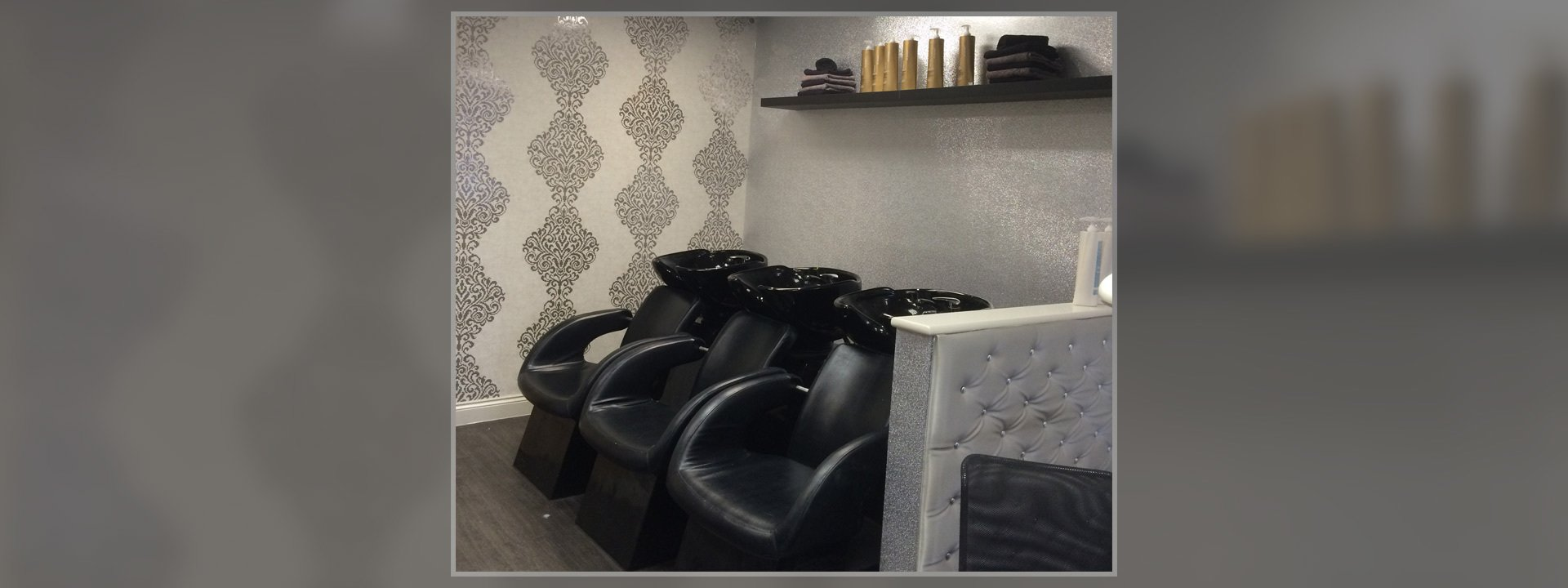 Black washbasins and black leather chairs at the hair washing station
