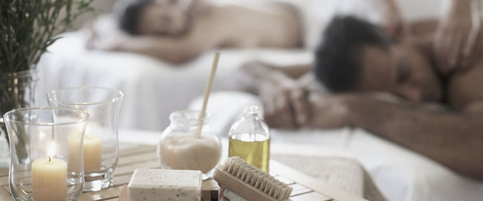 Candles, oils and soaps on a table near a man and woman having massage treatments