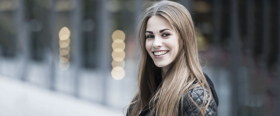 A smiling young lady with long light-brown hair