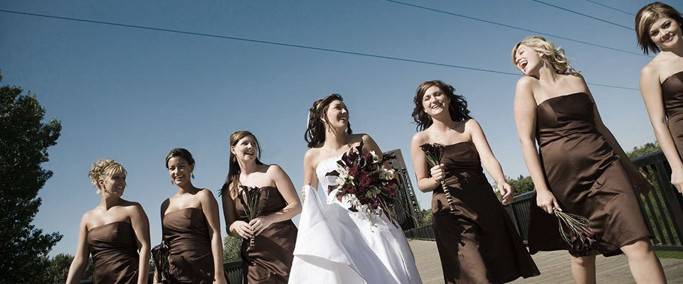 Bridesmaids in brown satin strapless dresses, on either side of a bride in white, with the colours of the bridesmaids' dresses picked up in her bouquet