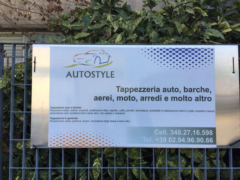 un cartello con scritto  Autostyle tappezzeria auto, barche,aerei,moto, arredi e molto altro