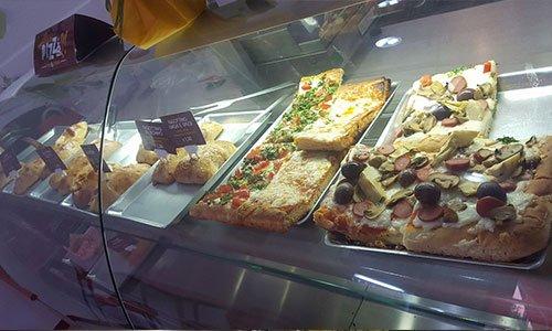 Pizze farcite con funghi, olive nere, mozzarella all'interno della vetrina del negozio