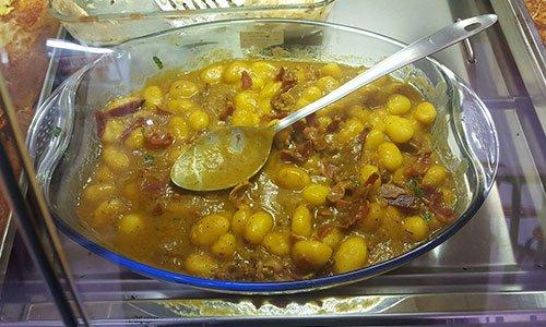 piatto di gnocchi e affettati in recipiente di vetro