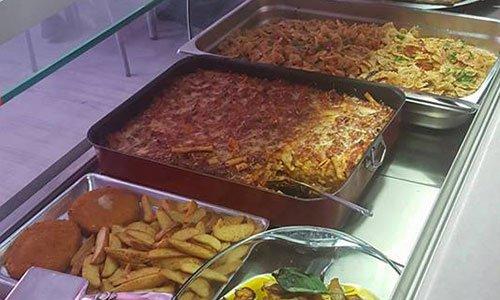 Pasta al forno, patate, cotolette e farfalle con verdure in esposizione nella vetrina