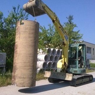 un mezzo da lavoro che carica un grosso tubo in ferro