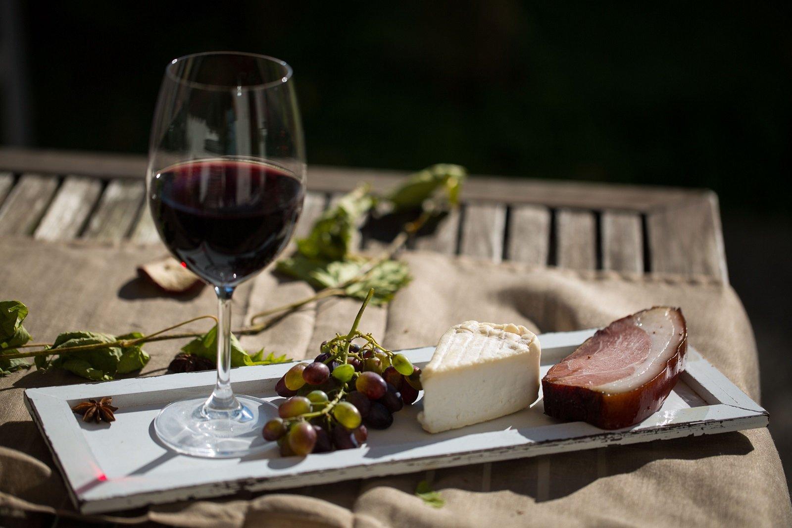 Coppa di vino rosso, uve,formaggio e speck