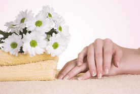Manicured hands beside a folded towel and white flowers