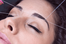 A lady having her eyebrows threaded