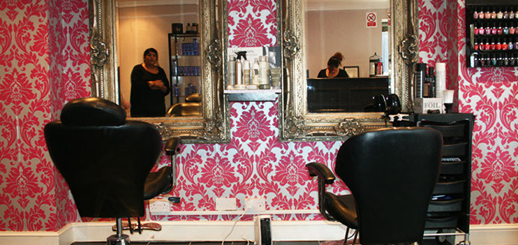 A stylist reflected in a mirror on a red and white wall