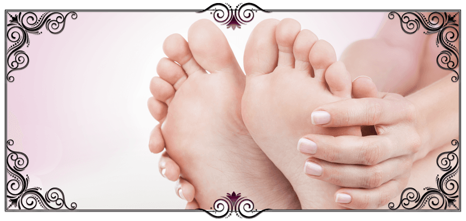 A lady holding her hands against her feet, showing manicured nails