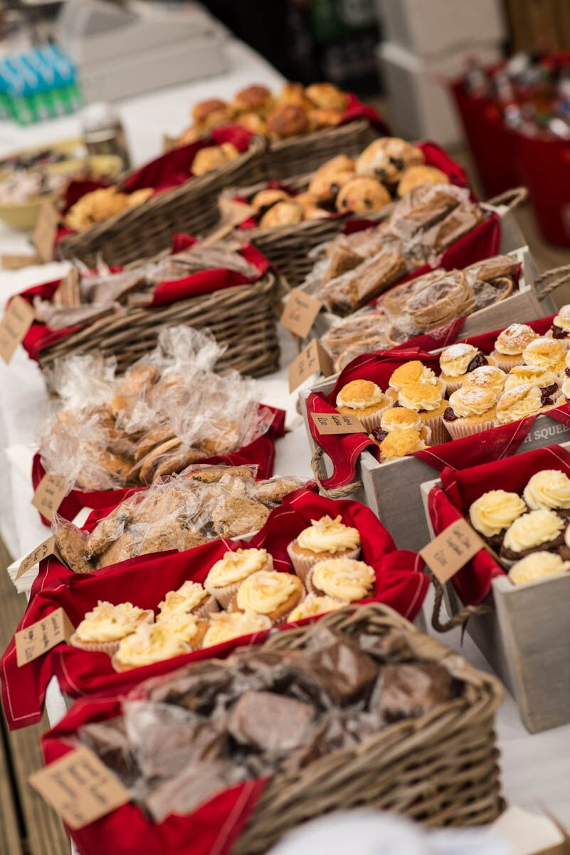 row of cakes and scones in baskets