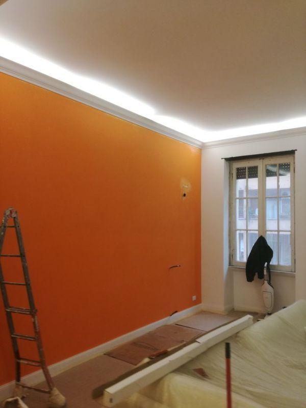 stanza con mura pitturanto in arancio ancora in fase di ristrutturazione