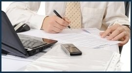 persona in cravatta che scrive davanti a un computer
