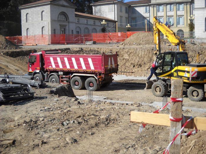 un cantiere con trattore, gru e materiali edili