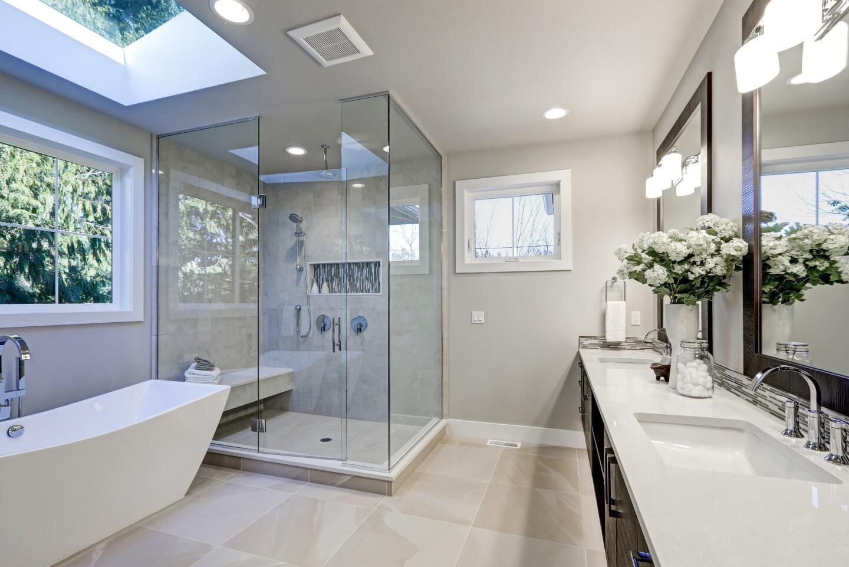 bagno con doccia in vetro e piani in marmo