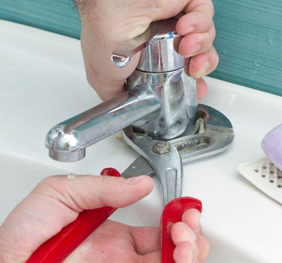 plumber adjusting faucet