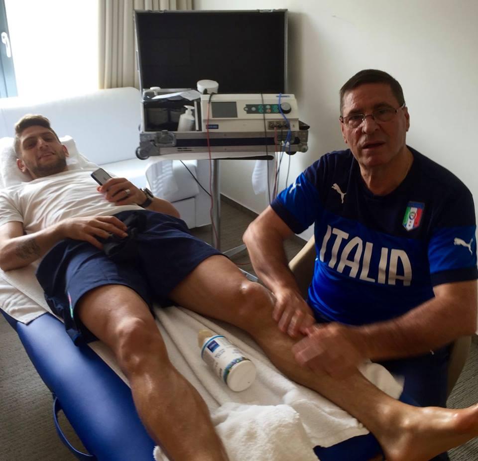 medico sportivo con maglietta dell`ITALIA massaggia la gamba a un atleta