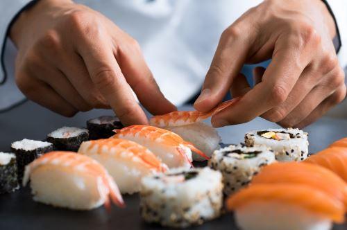 due mani che preparano del sushi