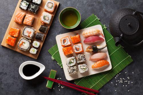 dei vassoi con del sushi, salsa di soya e bacchette