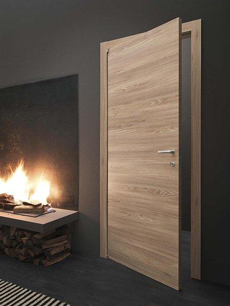 Bella porta in legno chiaro insieme a un camino