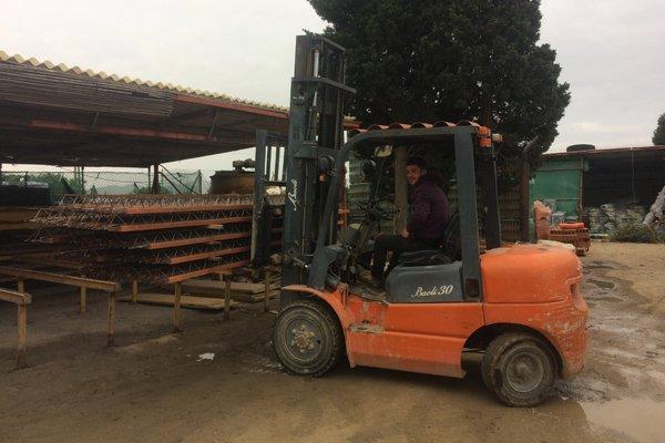muletto arancione con operaio che lo guida