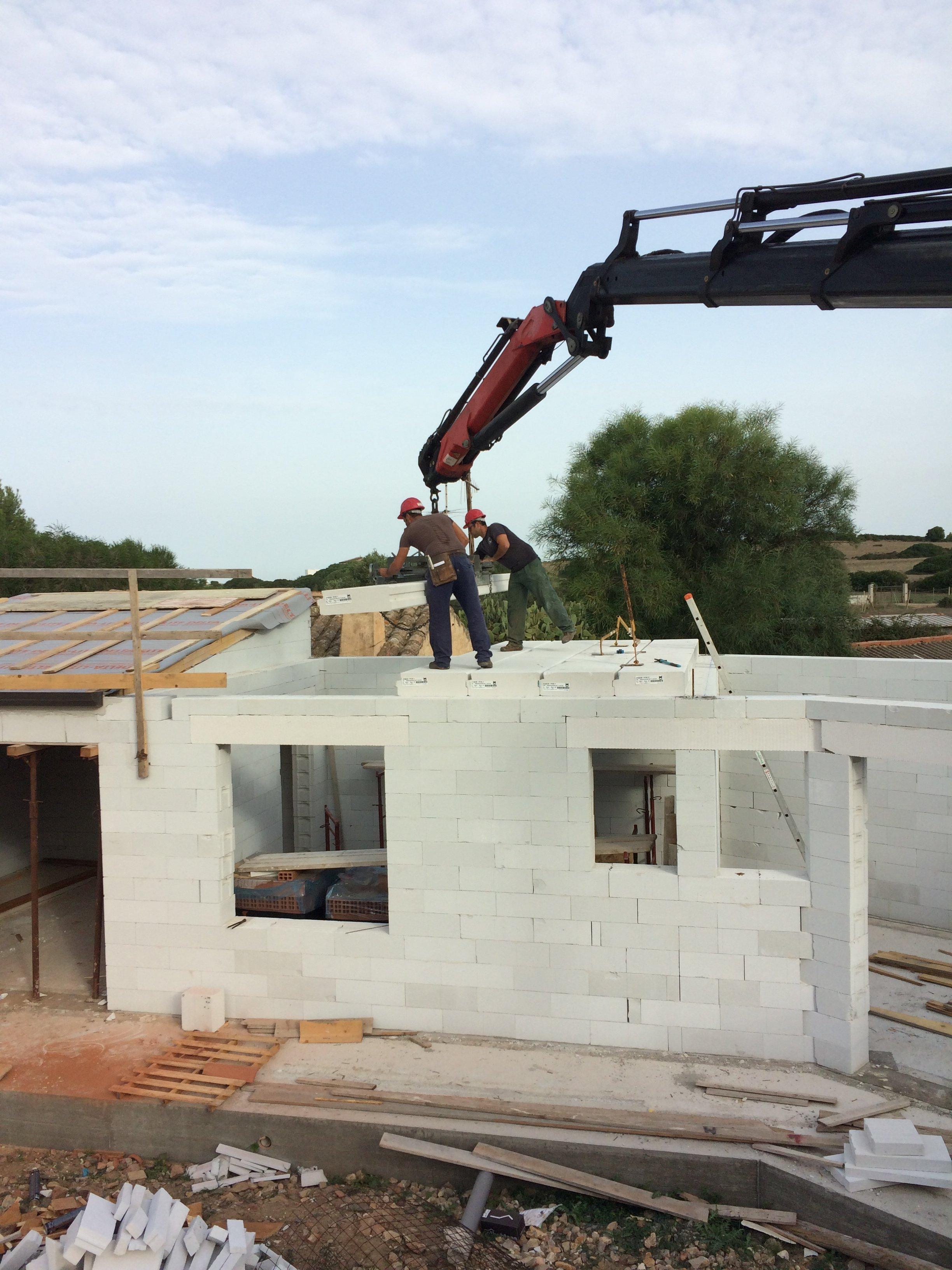 lavoratori su un tetto che ristrutturano una casa bianca